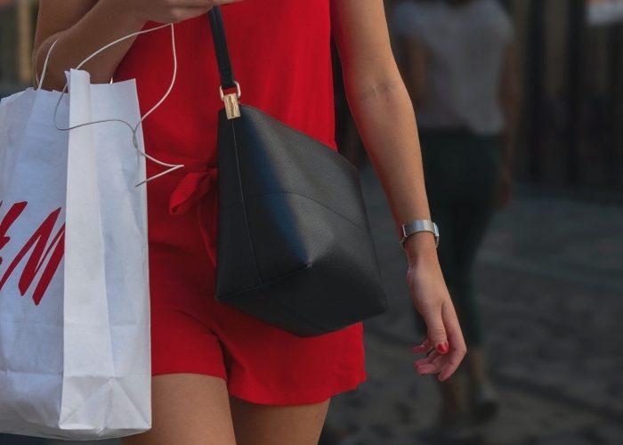 Woman holding H&M bag - fast fashion greenwashing cover image