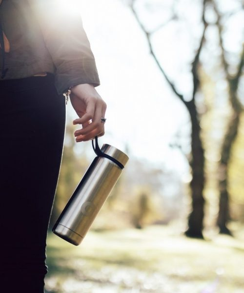 Woman with reusable water bottle walking in nature