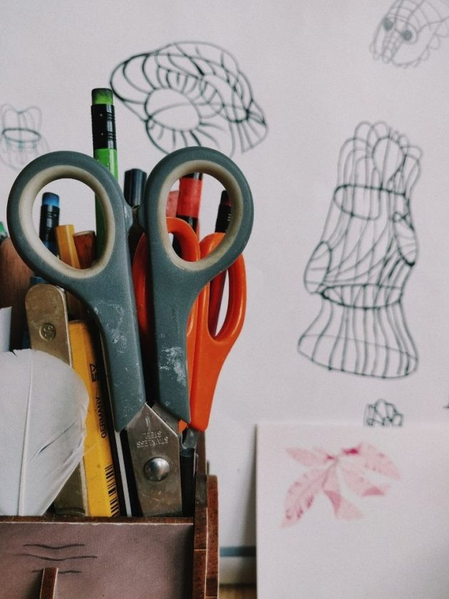 Scissors and pencils in basket with sketches in the background